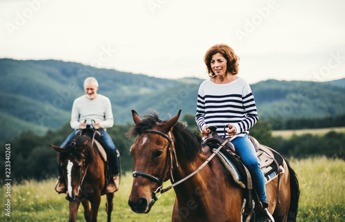 A senior couple riding horses in nature.