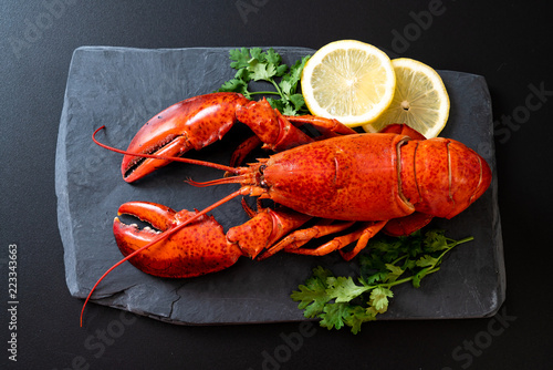 lobster with vegetable and lemon on black slate plate Fototapeta