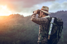 Hiker With Backpack Standing Looking Through Binoculars On The Mountain