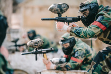 Selective Focus Of Paintball Player In Protective Mask Aiming With Marker Gun And His Teammate Behind Outdoors