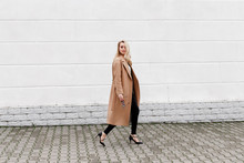 Beautiful Young Stylish Blonde Woman Wearing Long Beige Coat And Black High Heel Shoes Walking Through The City Streets. Trendy Casual Outfit. Street Fashion.