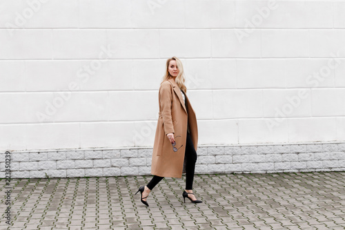 Beautiful young stylish blonde woman wearing long beige coat and black high heel shoes walking through the city streets Canvas Print