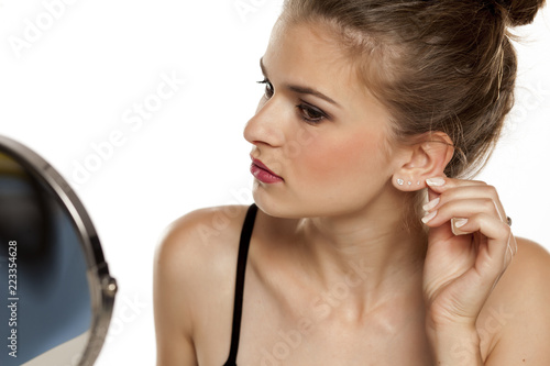 Profile of young woman touching her ear on white background Billede på lærred