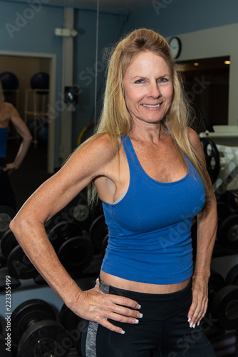 Fotografie, Obraz  Smiling middle age female content with life while posing in health club weight room