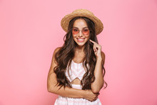 Photo Of Happy Woman 20s Wearing Sunglasses And Straw Hat Smiling At Camera, Isolated Over Pink Background