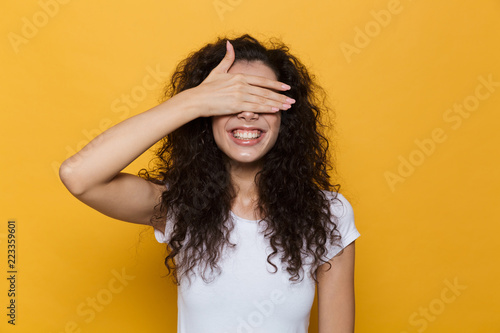 Fototapeta Image of brunette woman 20s with curly hair smiling and covering eyes with palm, isolated over yellow background obraz na płótnie