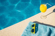 Fashion sunglasses, towel and juice near the pool