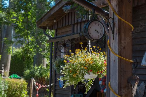 Fotografie, Obraz  Alte Holzhütte mit Wanduhr und Blumenampel