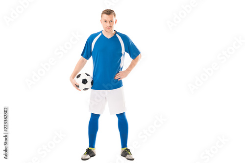 confident young soccer player holding ball while standing with hand on waist and looking at camera isolated on white