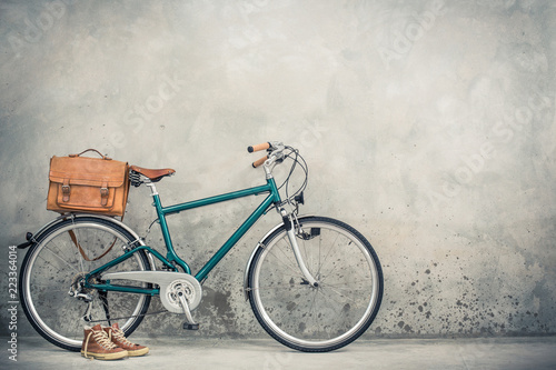 Fotobehang Fiets Retro bike with aged leather postman's bag and old sneakers front concrete wall background. Vintage style filtered photo