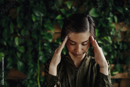 Focused young woman at wall with climbing plants