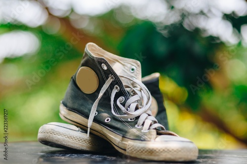 Old shoes black sneakers with bokeh background Fototapeta