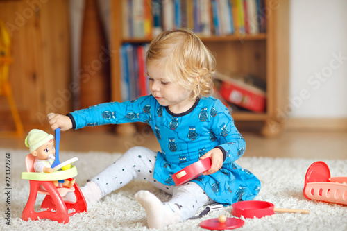 Adorable cute little toddler girl playing with doll Tableau sur Toile