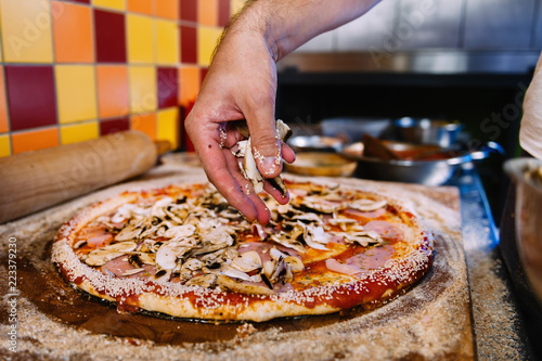 Door stickers Pizzeria Putting Mushrooms On Pizza In Pizza Restaurant
