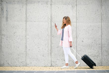Woman Carrying Luggage And Usi...