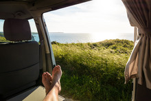 First-person View Of A Barefoot Man Relaxing Inside A Camper Van And Enjoying The View Over The Sea At Sunset Through The Open Sliding Door With Wild Grasses In The Foreground.