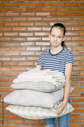 unhappy preteen girl holding stack of pillows and blankets against brick wal. Homework, cleaning concept