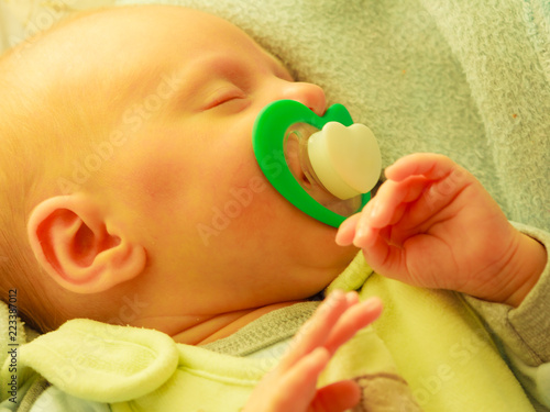 Fotografía Closeup of little newborn sleeping with teat in mouth