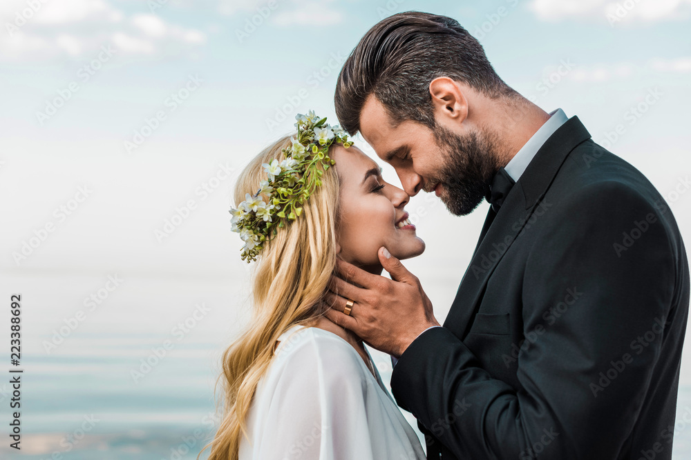 Fototapeta happy wedding couple in suit and white dress touching with noses on beach