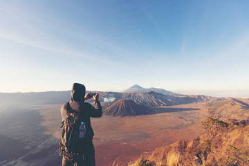 successful man hiker taking picture with smartphone at cliff edge on mountain top of volcano bromo Indonesia travel at sunrise time.