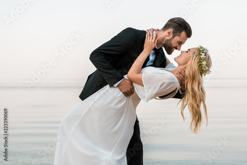 affectionate wedding couple going to kiss on beach Fotobehang