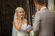 canvas print picture - Amazing bride is speaking a oath to his groom during wedding ceremony, standing near the exclusive wedding arch. Outdoors.