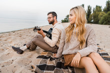 Handsome Boyfriend In Autumn Outfit Playing Acoustic Guitar For Girlfriend On Beach