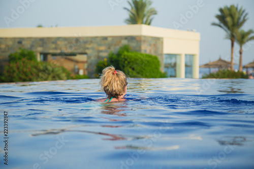 Fotografía  View from back of white european tourist swimming in blue water of outdoor pool at tropical hotel resort