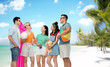 friendship, travel and summer holidays concept - group of happy smiling friends in sunglasses with ball, volleyball, towel, camera and air mattress over tropical beach background in french polynesia