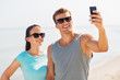 fitness, sport and lifestyle concept - happy couple in sports clothes and sunglasses taking selfie by smartphone on beach