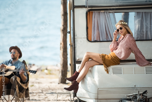 hippie girl sitting on campervan while her boyfriend playing guitar near the sea Tablou Canvas