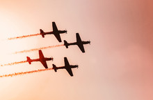 Squad Of Four Airplanes Flying Together Leaving A Smoke Trail Behind, Photo At A Sunset. Warm Colours. Space For Text On Sky.