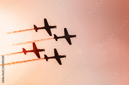 Fotografija  Squad of four airplanes flying together leaving a smoke trail behind, photo at a sunset