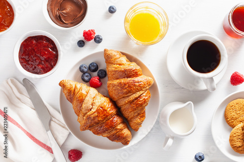 Fototapeta Continental breakfast with croissant, jam, chocolate spread and coffee. Top view obraz
