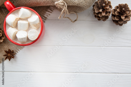 Spoed Foto op Canvas Chocolade Christmas red cup with hot chocolate and marshmallow. Hot cocoa with milk, anise on white wooden rustic background, hessian (sacking) top view. Copy space.