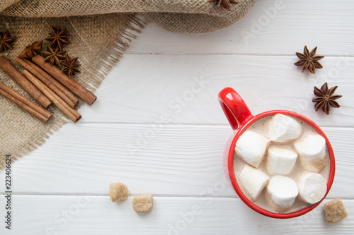 Christmas red cup with hot chocolate and marshmallow. Hot cocoa with milk, anise and cinnamon sticks and brown sugar on white wooden rustic background, hessian (sacking) top view.