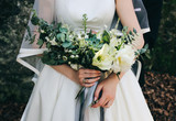 Groom is hugging beautiful bride in satin atlas dress is standing outdoors in the autumn forest. Elegant wedding bouquet from eustoma , white peony and eucalyptus with grey ribbon. Wedding couple.