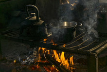 A Pot And A Kettle Stand Over A Fire On A Portable Hearth Made Of Metal Rods In A Nomad's Dwelling..