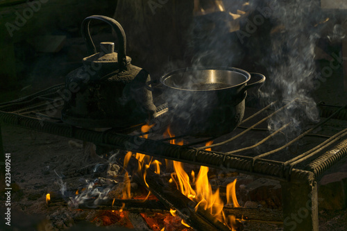 a pot and a kettle stand over a fire on a portable hearth made of metal rods in a nomad's dwelling Canvas Print