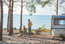 Hippie Couple Having Picnic With Guitar At Trailer Near The Sea