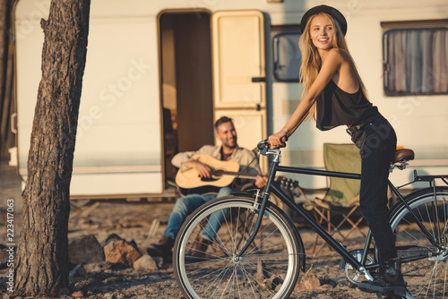 Fotografie, Tablou  selective focus of happy girl with bicycle and man playing guitar near trailer