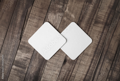 Two blank square beer coasters on wood background. Flat lay.