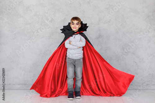 Smiling boy vampire portrait with crossed hands
