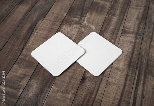 Photo of two blank white square beer coasters vintage wood table background.
