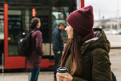 plakat A girl drinks coffee from a disposable cup on the street in Prague near the tram stop. The usual urban everyday life.