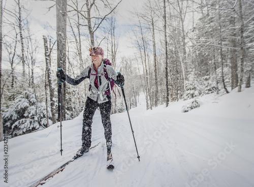 Fotobehang Wintersporten Woman skiing in forest in winter