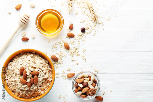 Oatmeal in bowl with nuts on white wooden table