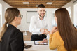 Cheerful male applicant happily shaking employer hand. Young man in shirt spending time on job interview in modern office