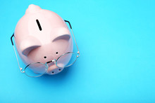 Pink Piggy Bank With Glasses On Blue Background