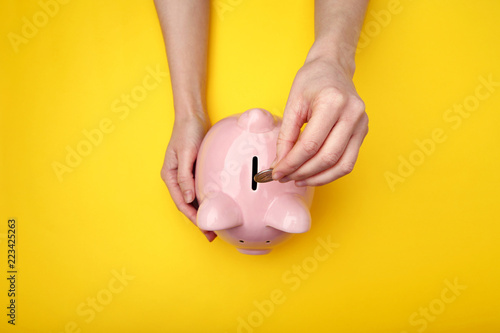 Fotografia  Female hand putting coin into piggy bank on yellow background
